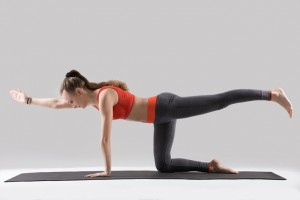 Young attractive woman practicing yoga, standing in Bird dog exercise, Donkey Kick pose, working out, wearing sportswear, red tank top, pants, indoor full length, isolated, grey studio background